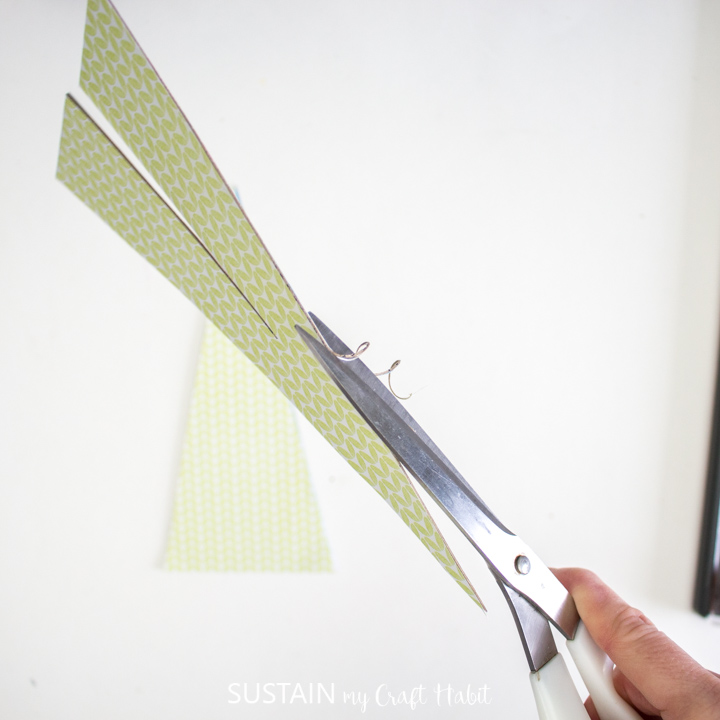 Trimming excess paper with scissors.