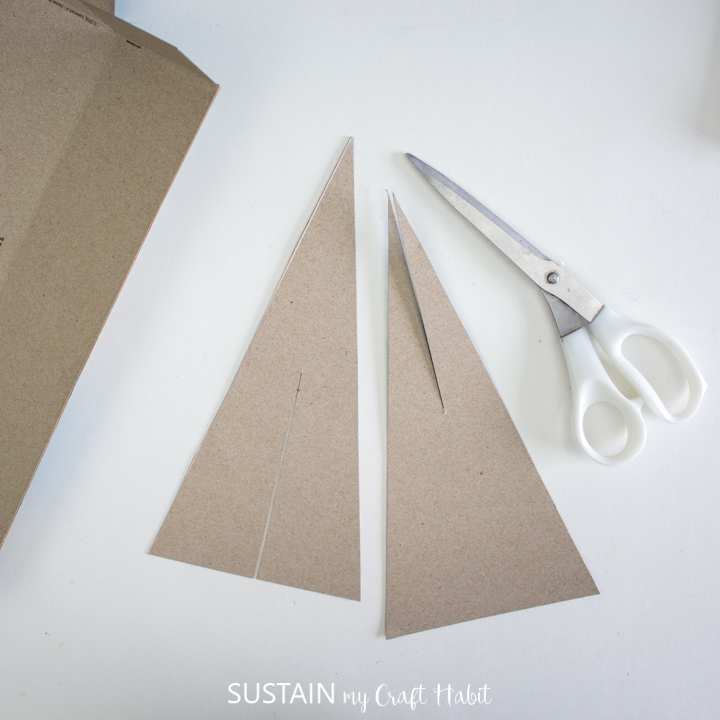 Cutting out Christmas tree shapes from the cardboard.