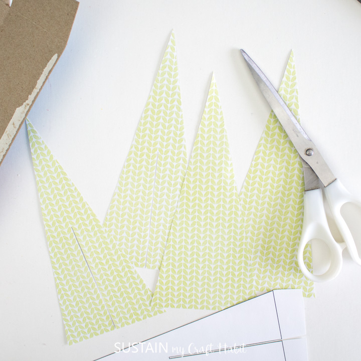 Using the pattern to cut out Christmas tree shapes from scrapbook paper.