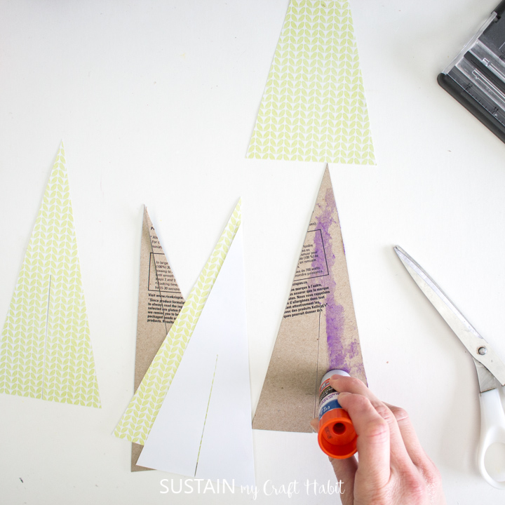 Adding glue to the cut out cardboard trees.