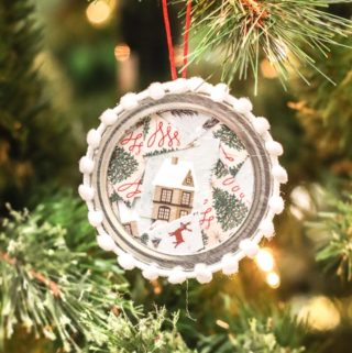 Canning jar lid ornament hanging from a tree.