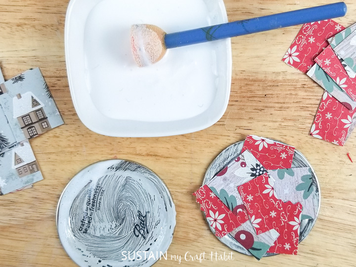 Adding mod podge to a mason jar lid and covering with fabric squares.