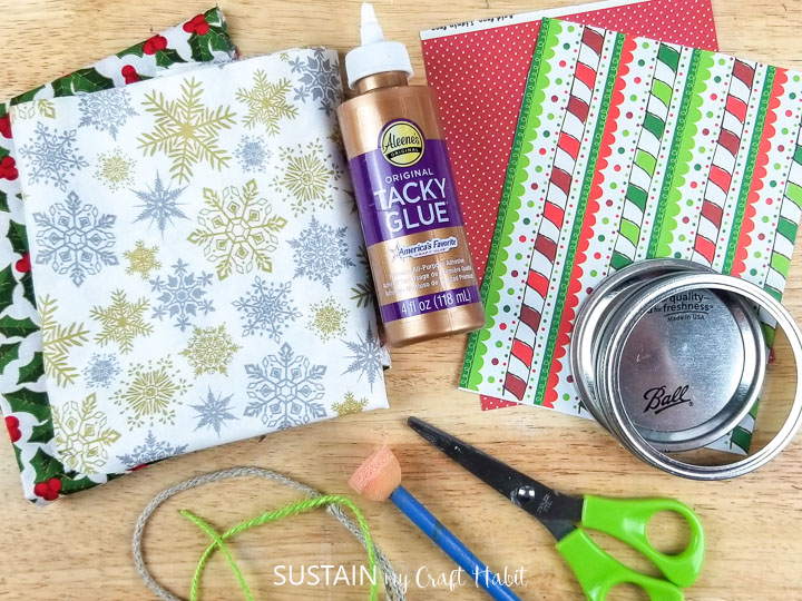 Materials needed to make Christmas canning jar lid ornaments.