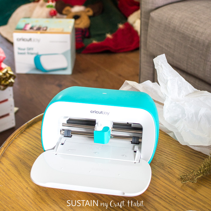 Cricut Joy placed on a table in front of a Christmas tree