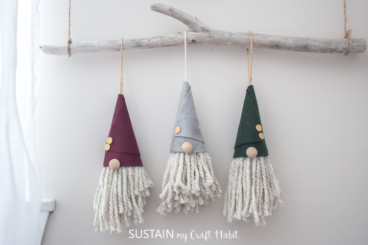 Three completed gnome christmas ornaments, hanging side by side on a branch of white-washed driftwood against a beige wall.