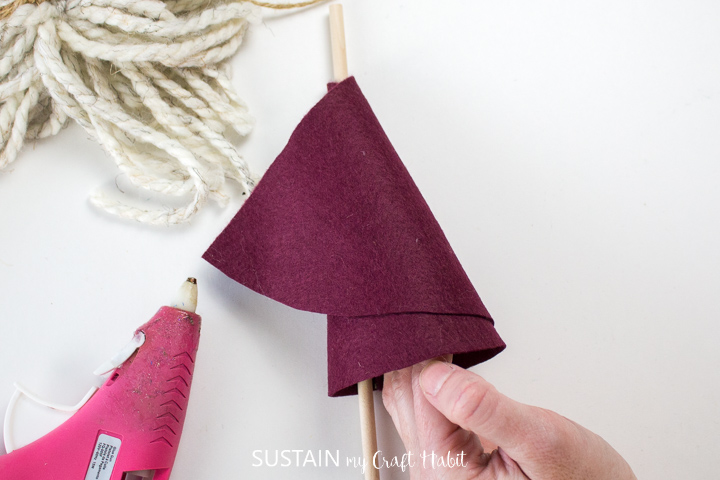Wrapping the felt fabric around the wooden dowel.