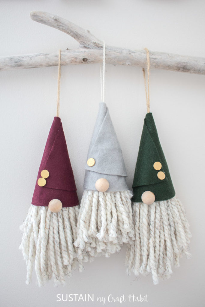 Gnome Christmas ornaments hanging on a tree branch.