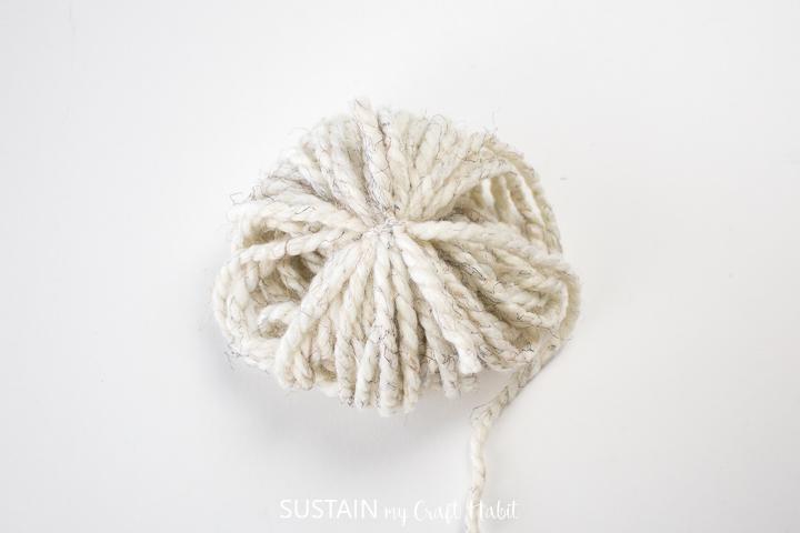 Tightening the yarn around the wrapped yarn.