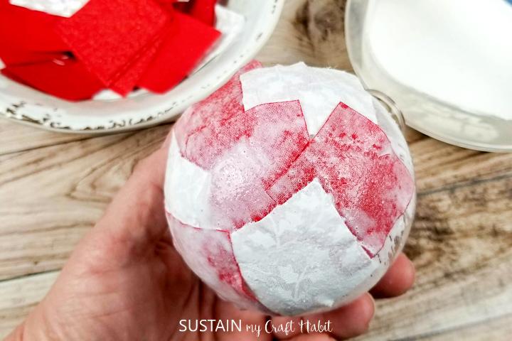 Gluing fabric squares onto a glass ornament.