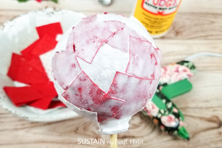 Adding a second layer of mod podge onto a glass ornament.