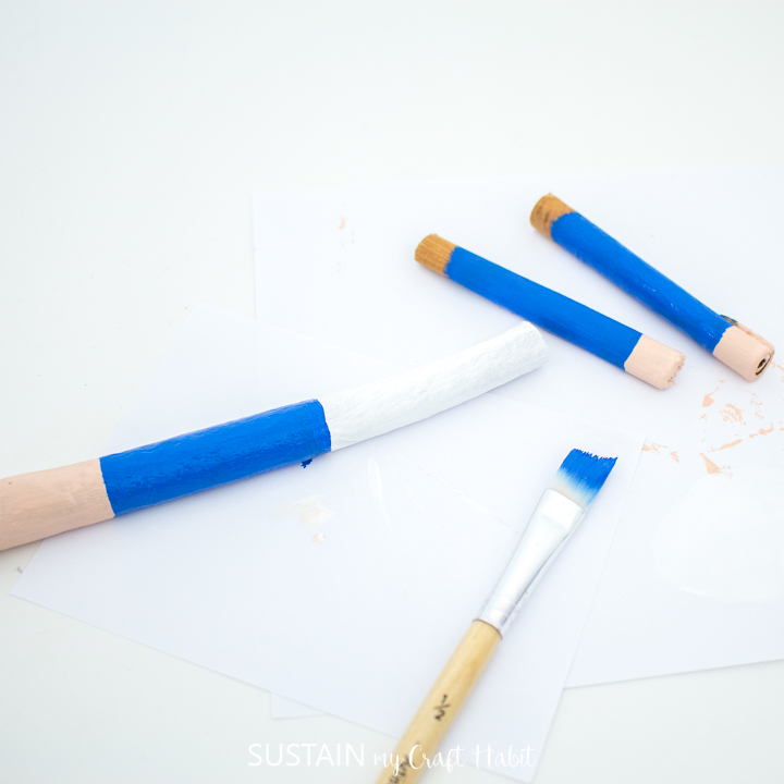 Painting the middle of the cinnamon stick with blue paint.