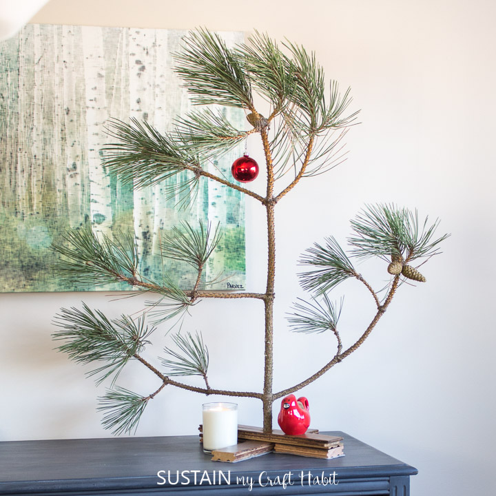 a complete Charlie Brown tree placed on top of a dining room hutch