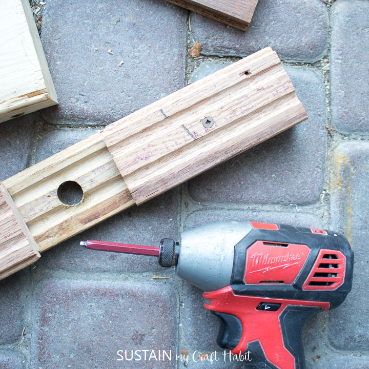 Using a drill to screw in small wooden boards to the bottom of the long board.