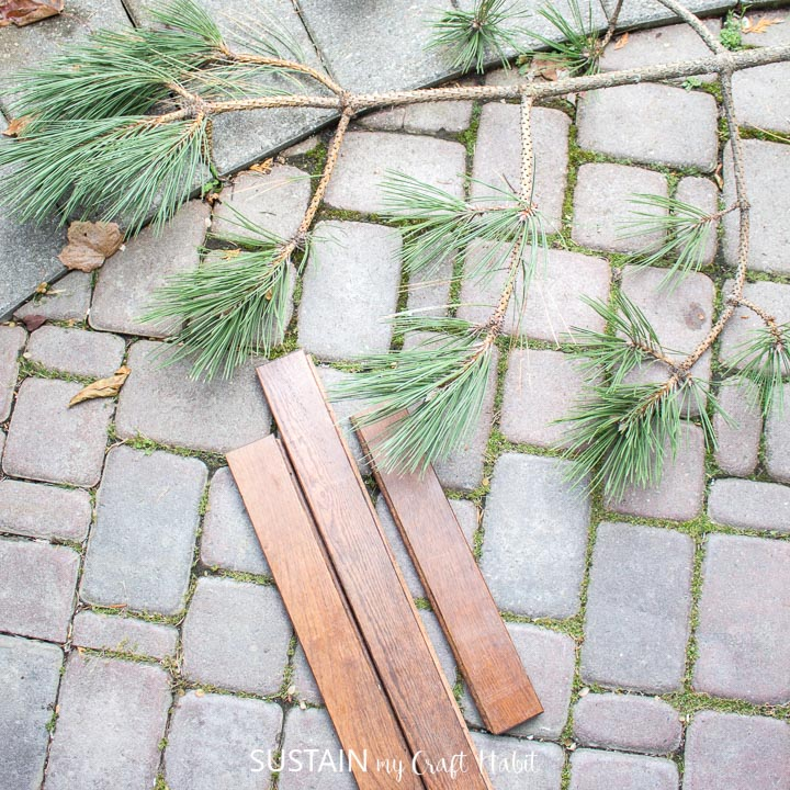 A piece of pine tree and wood planks on a stone path.