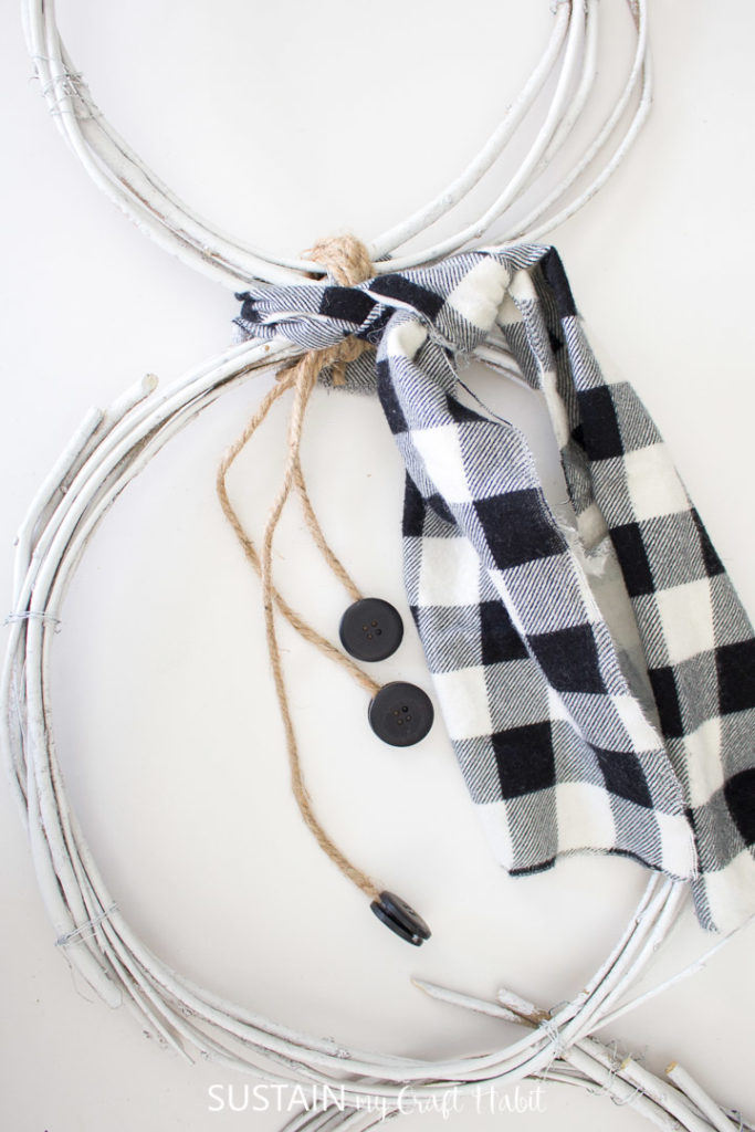 Tying the plaid fabric to the snowman wreath.