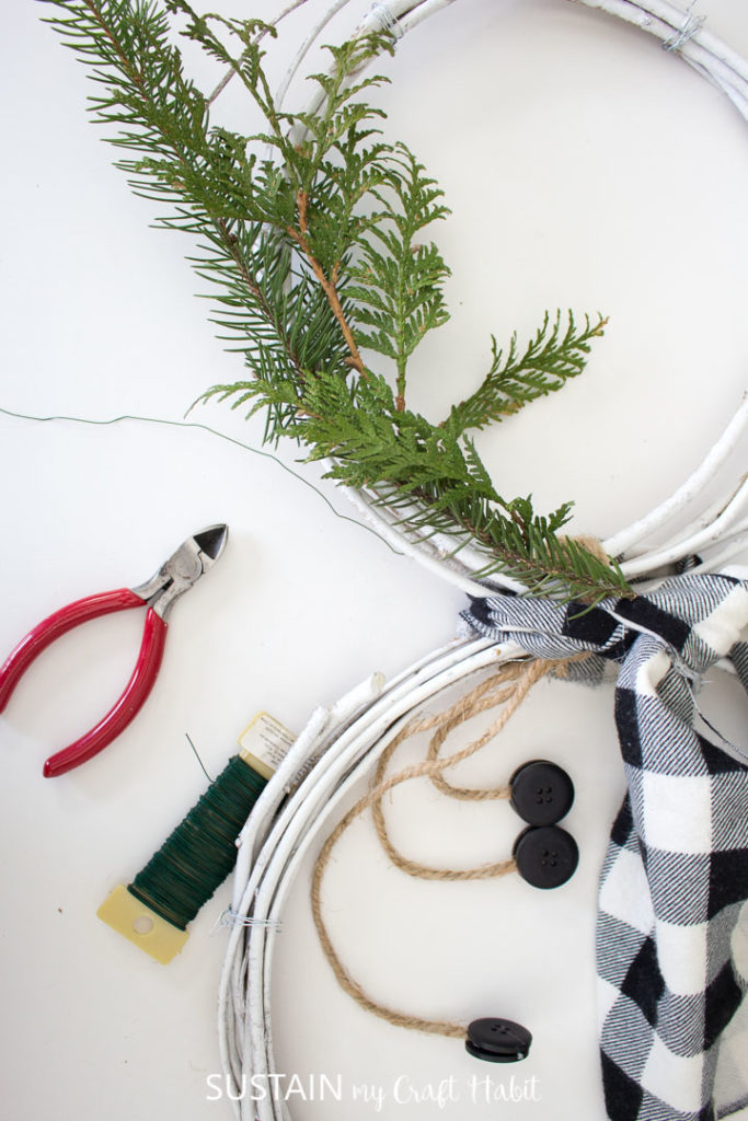 Securing green foliage to the snowman wreath.
