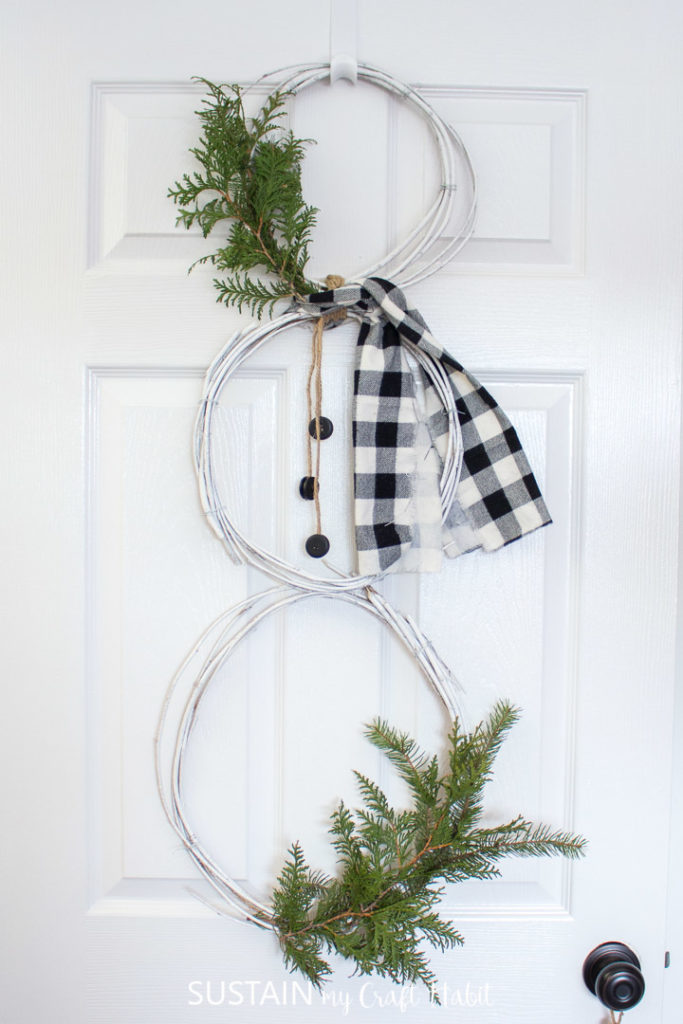 Snowman wreath made from mulberry vines hanging from a door.