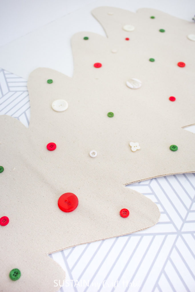 Adding colorful buttons onto the canvas Christmas tree.
