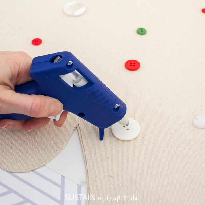 Hot gluing buttons onto the canvas Christmas tree.