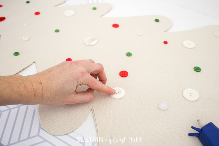 Pressing a button with hot glue onto the canvas Christmas tree.
