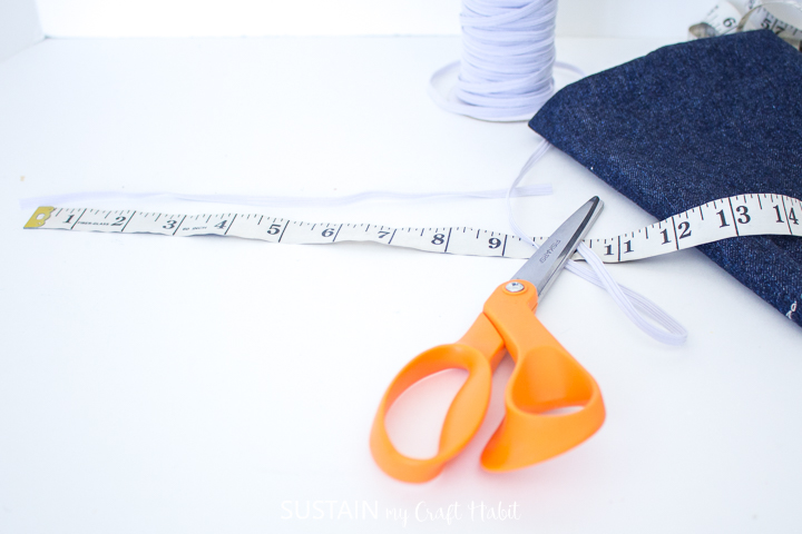 Measuring and cutting a piece of elastic.