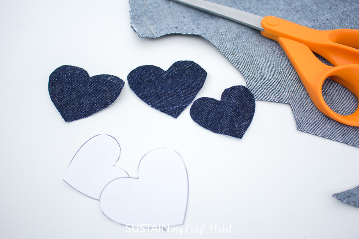 Cutting out denim hearts around the paper pattern.