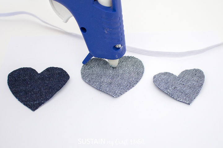 Adding hot glue to the cut out denim heart.
