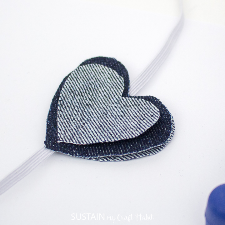 Hot gluing a smaller denim heart over top of the other heart cutout.