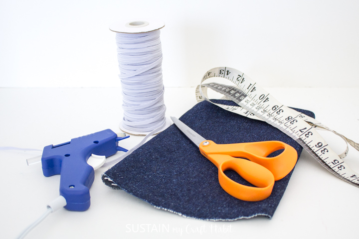 Materials needed to make elastic book bands including denim, measuring tape, scissors, elastic and a hot glue gun.