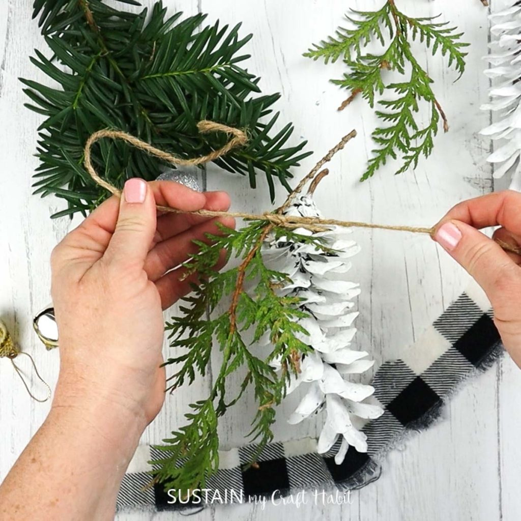 tie pine cone and greenery together with twine