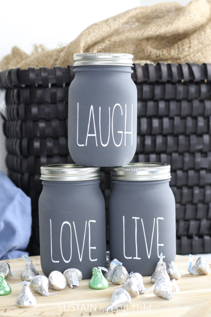 "Finished chalky painted jars with lettering ""laugh,"" ""love,"" and ""live"" on the front. Placed next to a basket and chocolates."