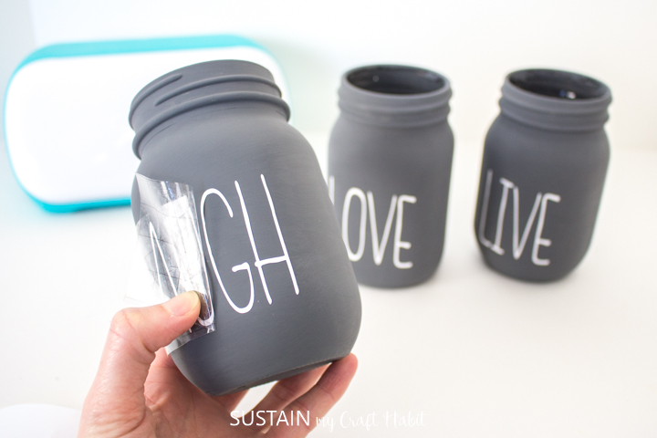 Peeling away the excess transfer tape from the remaining chalky painted mason jars.