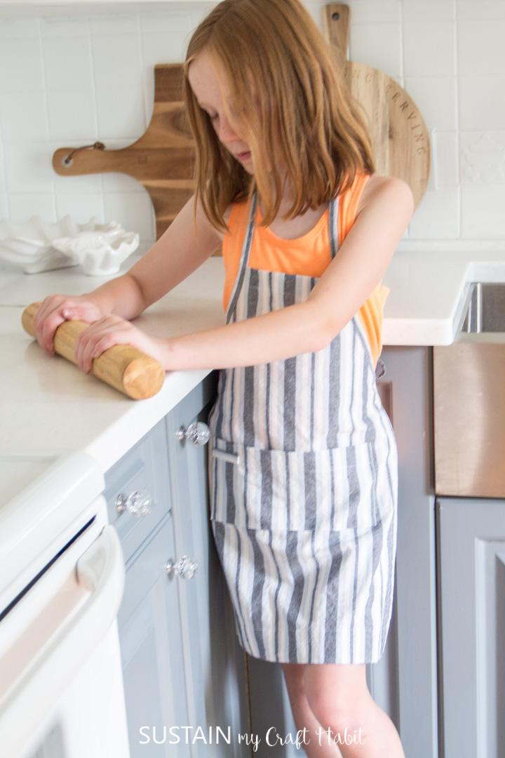 child wearing handmade apron in kitchen