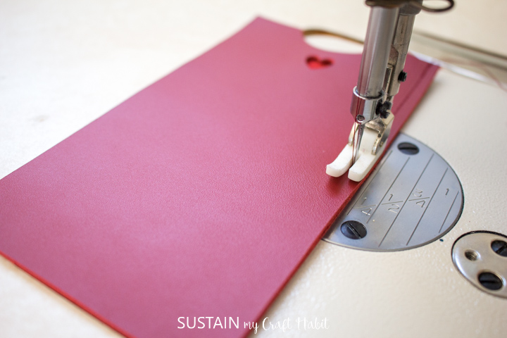 Sewing the red leather phone sleeves together.