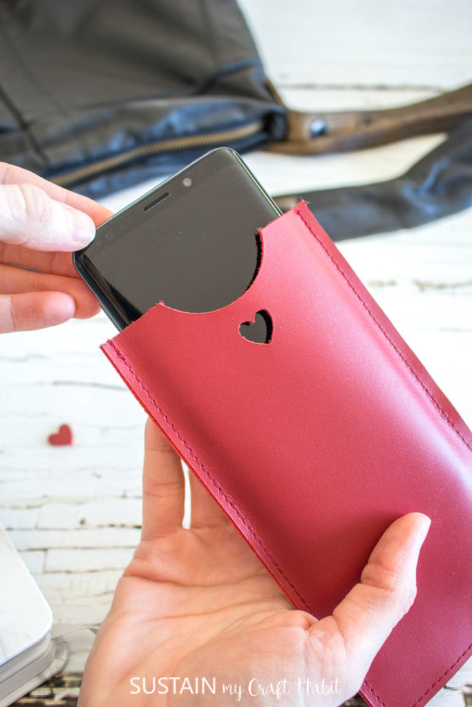 Inserting a cell phone into a red leather phone sleeve.
