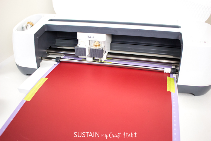 Cricut machine cutting the red leather.