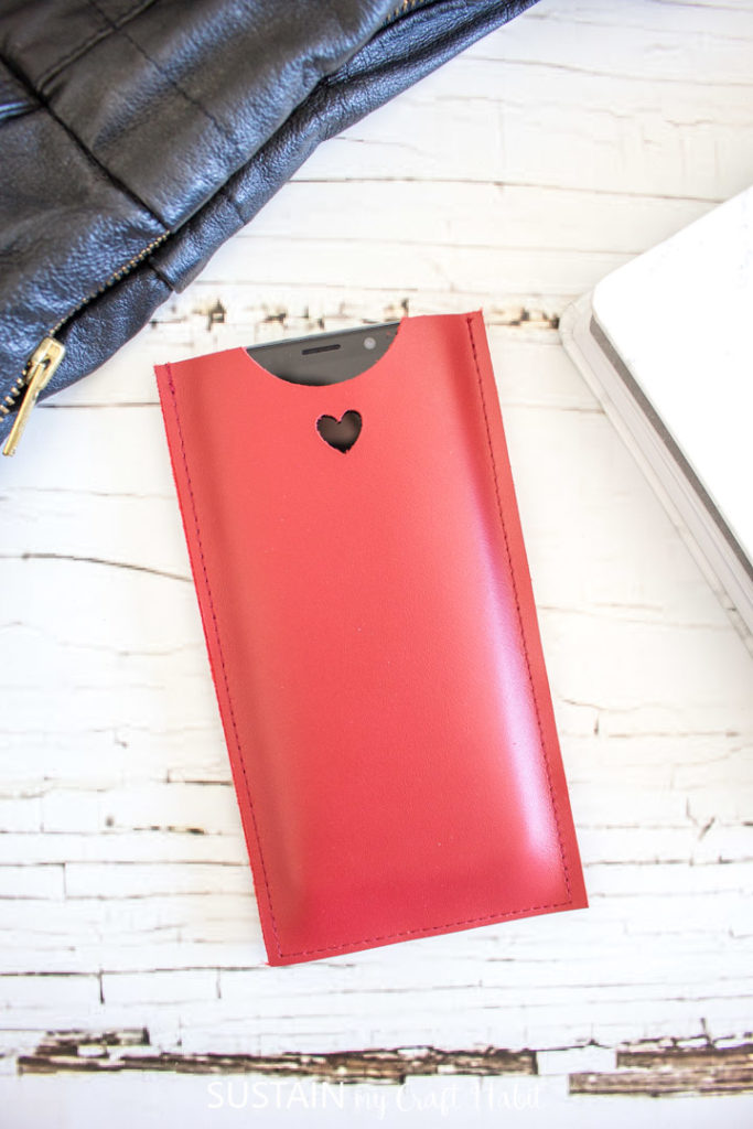 A cell phone inserted into a red leather phone sleeve.