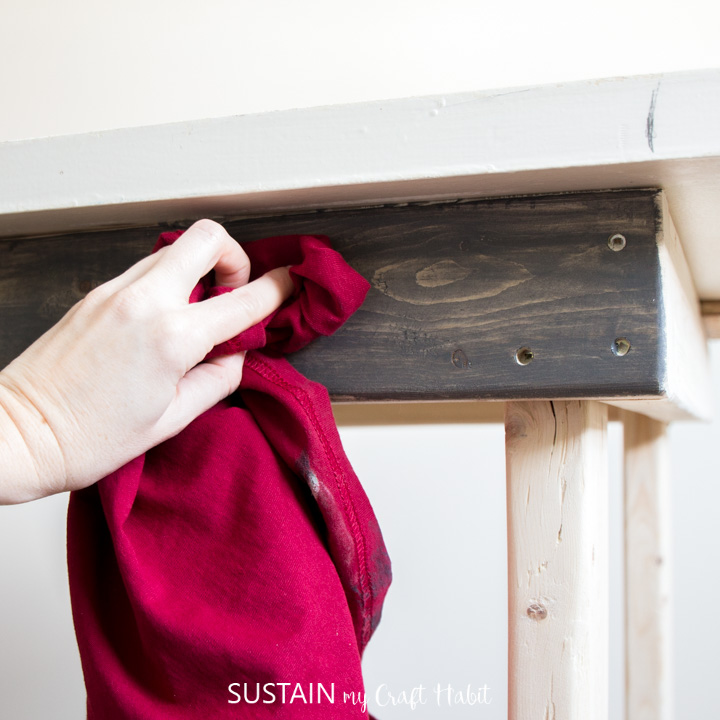 Using a rag to remove excess stain.