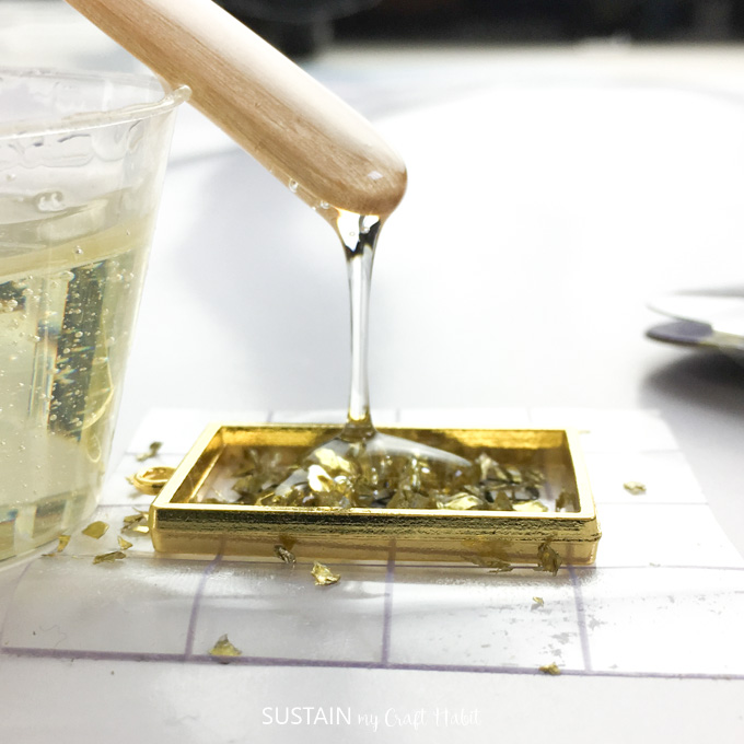 Pouring small amounts of resin into a gold bezel.