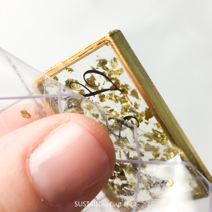 Peeling away tranfer tape to leave a monogram on the resin.