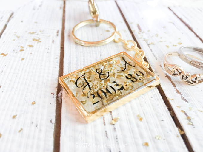 Resin keychain with gold flakes laid on a wood background.