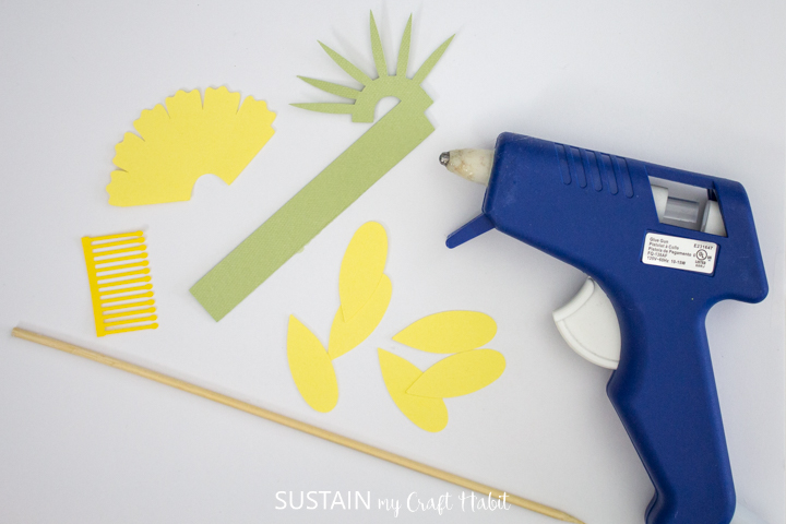 Materials needed to make daffodil paper flowers including a wooden dowel, hot glue gun and cut paper.