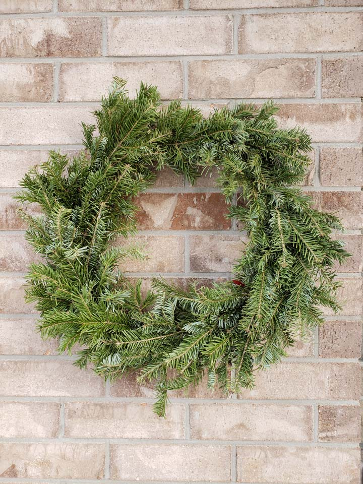 An evergreen wreath hanging against a brick wall.