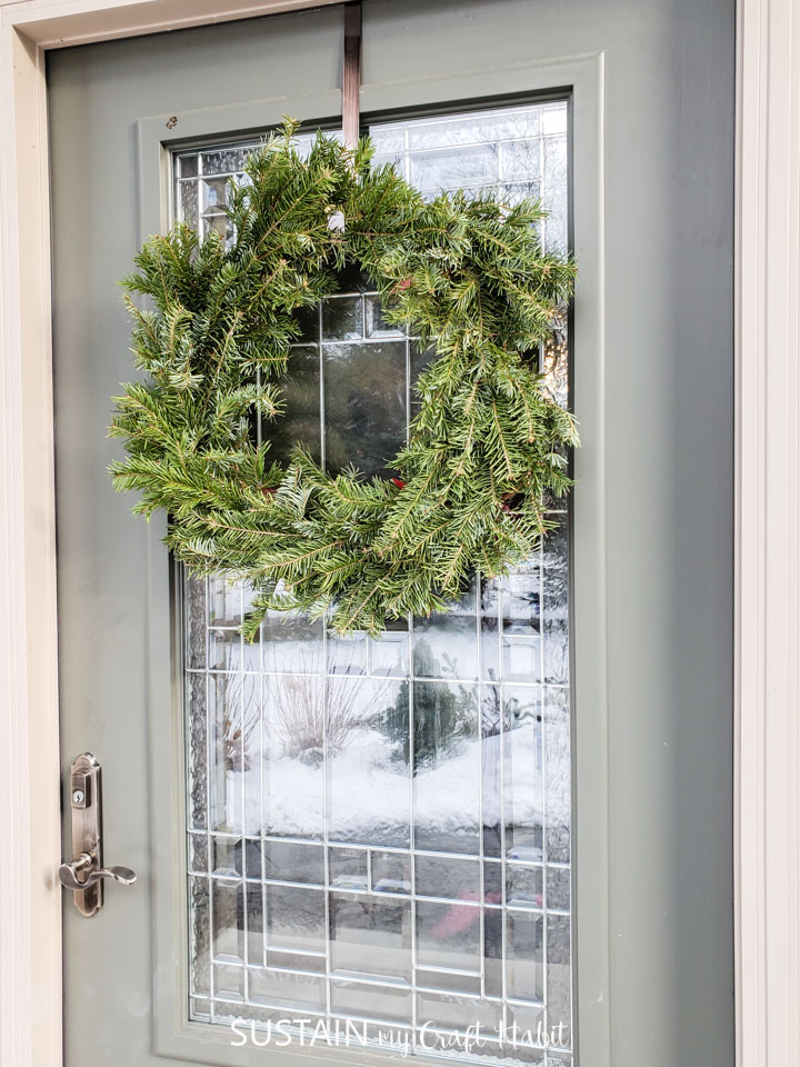 An evergreen wreath hanging from a door.