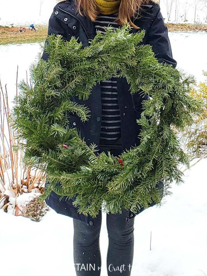 Woman holding a finished evergreen wreath.