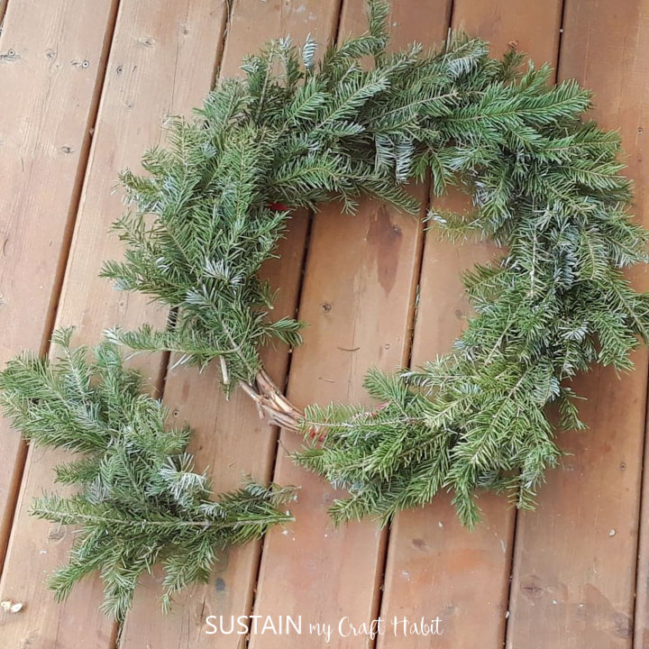 Layering evergreen trimmings on the grapevine wreath.