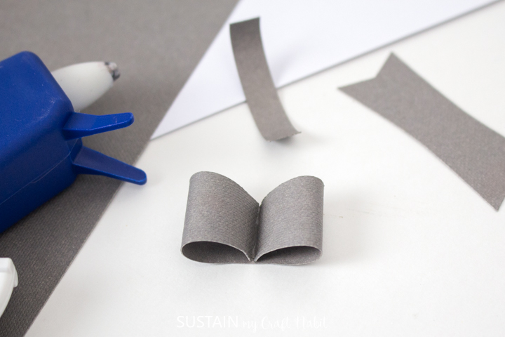Folding the curled edges into the middle of the paper bow.
