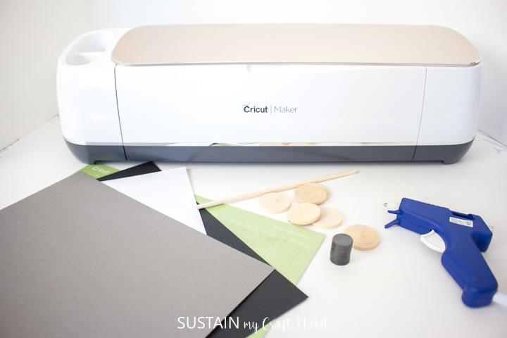Materials needed to make paper bow magnets including Cricut machine, paper, wood circles, magnets and hot glue gun.