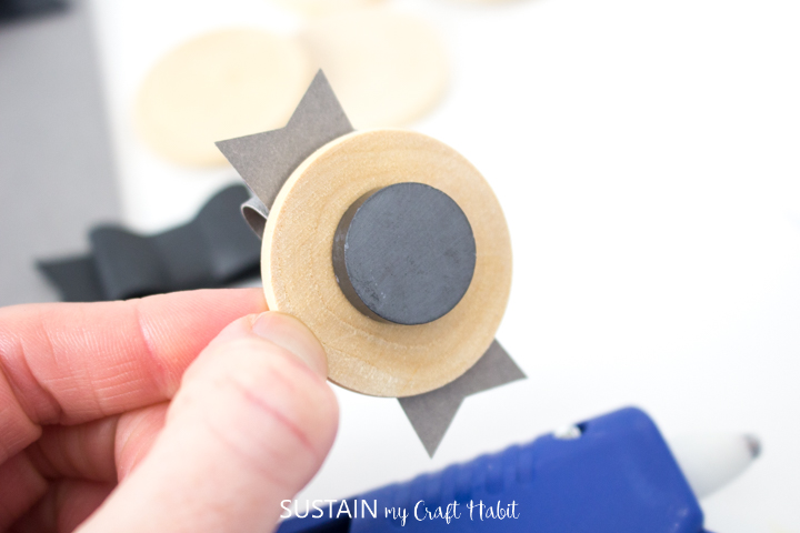 Gluing a magnet to the back of a wood circle.