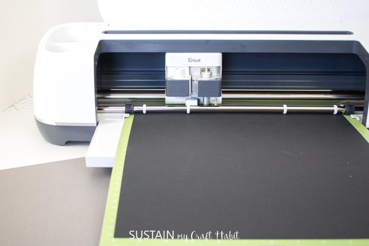 Black cardstock getting cut in Cricut machine.